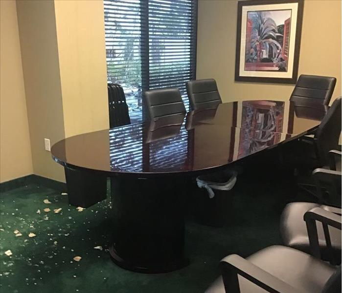 debris of the ceiling on the floor of the carpet and water on the floor.